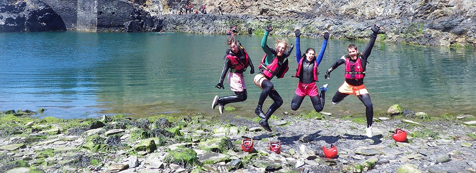 Adults jumping at the Blue Lagoon Abereiddy while Coasteering in Pembrokeshire Wales