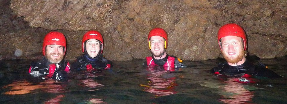 Adults exploring sea caves while coasteering at Abereiddy near St Davids in Pembrokeshire