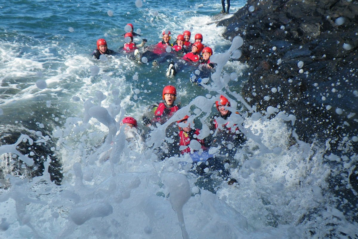 Adults adventure swimming in the washing machine rough water feature while Coasteering in North Pembrokeshire Wales.