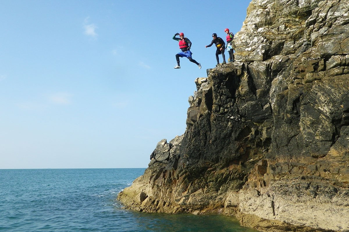 Cliff Jumping. Military group of adults leading into Wales' Celtic Sea