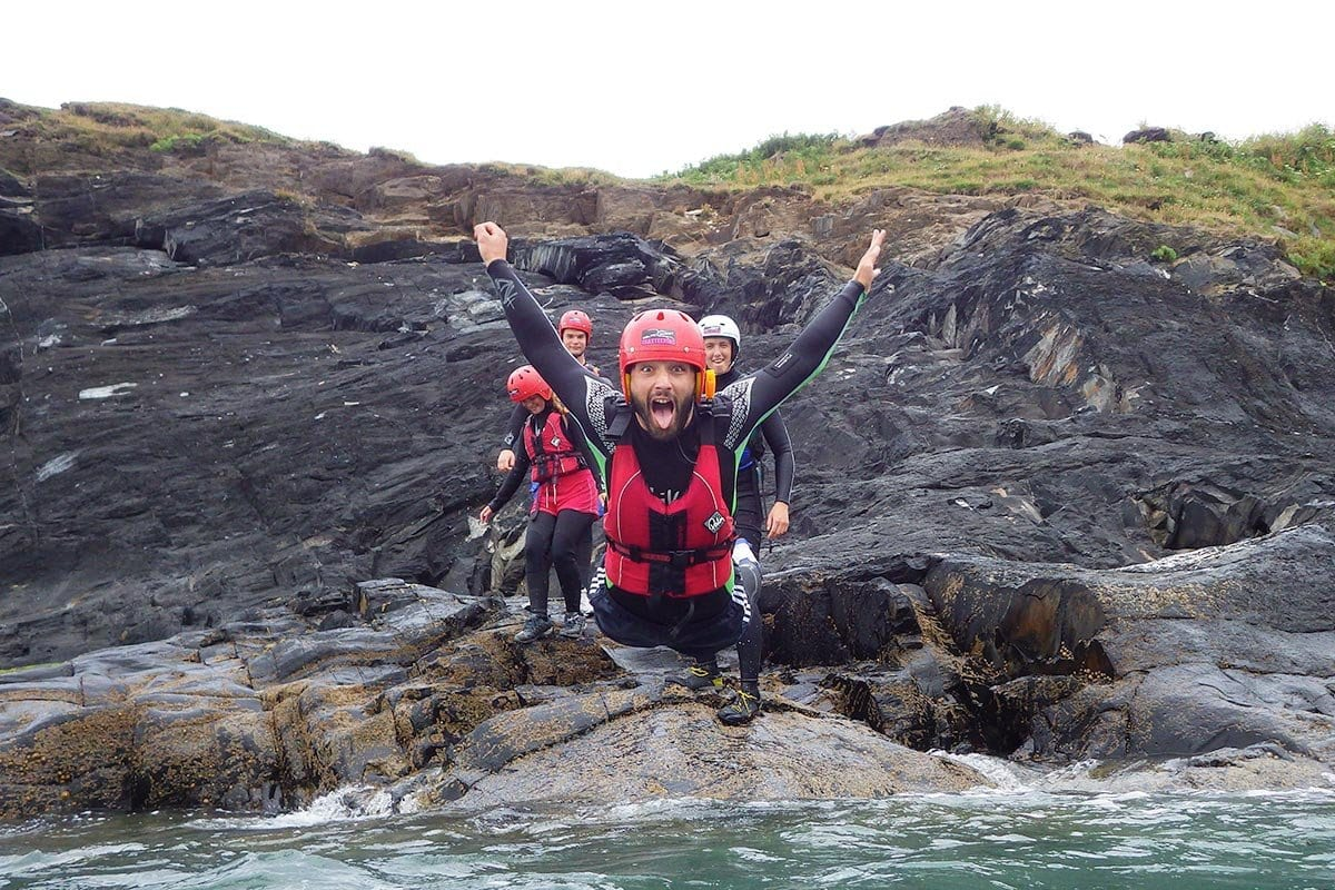Coasteering - scramble climb your way along Pemborkeshire's coast. Adults belly flopping into the Welsh sea