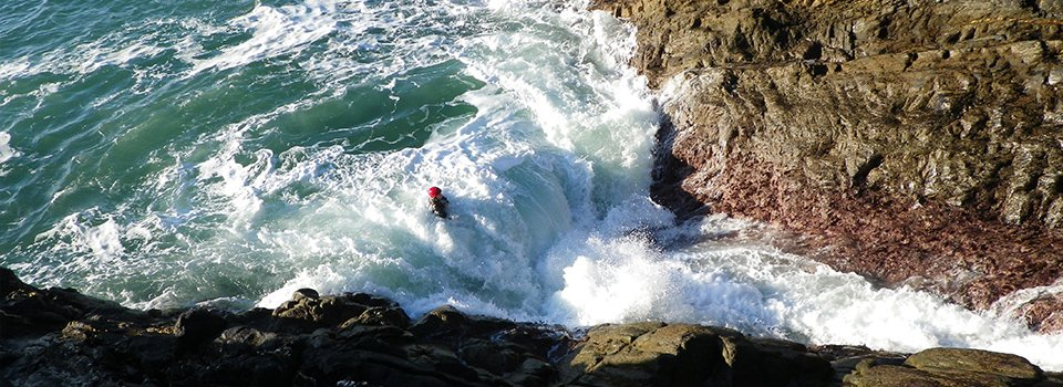 Big waves rolling into the Tumble Dryer while Coasteering in Pembrokeshire