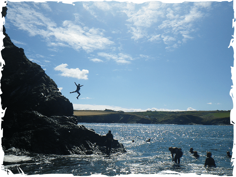 Adults Cliff Jumping while Coasteering in Pembrokeshire Wales