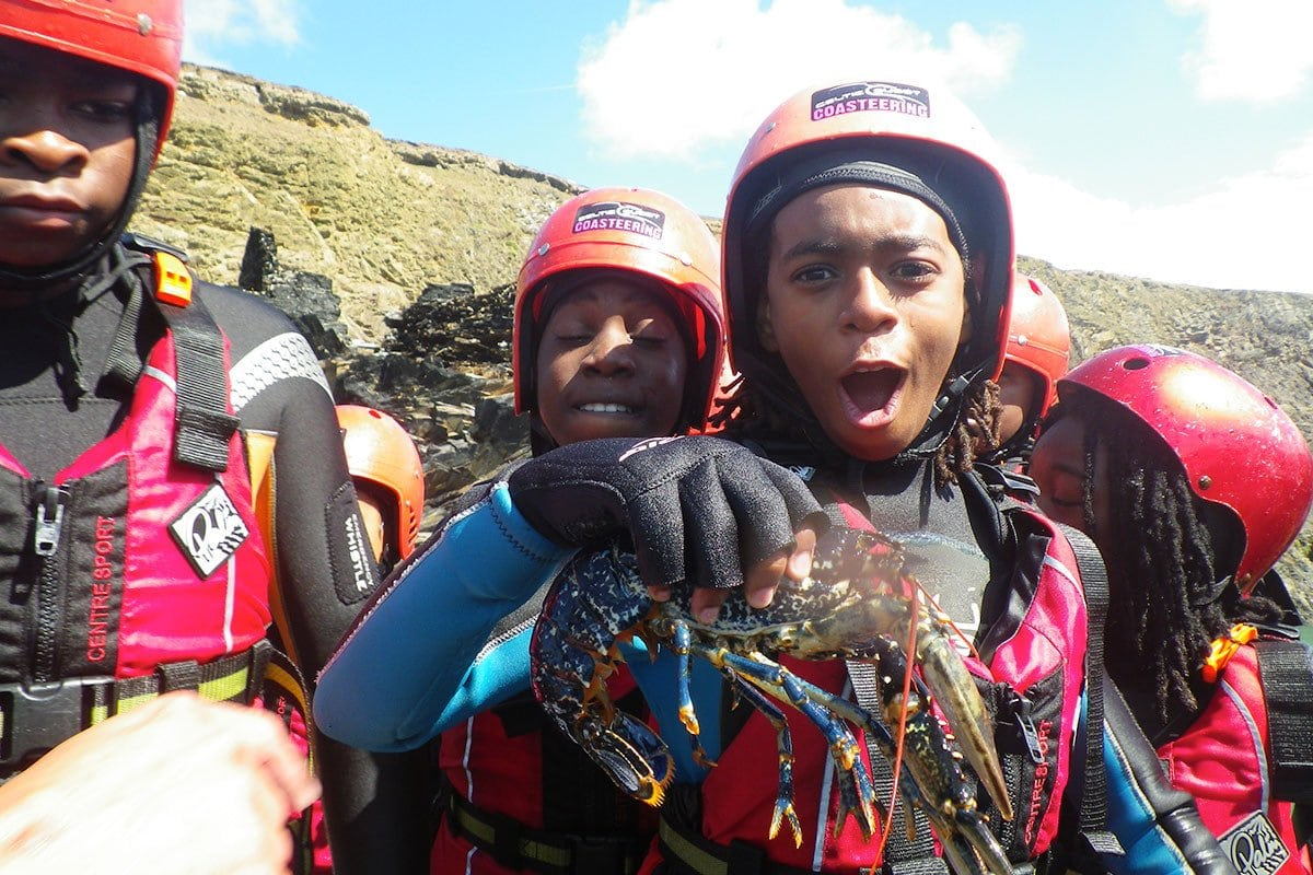 Coasteering Guides hand a live lobster to children adventuring on the Pembrokeshire coast.