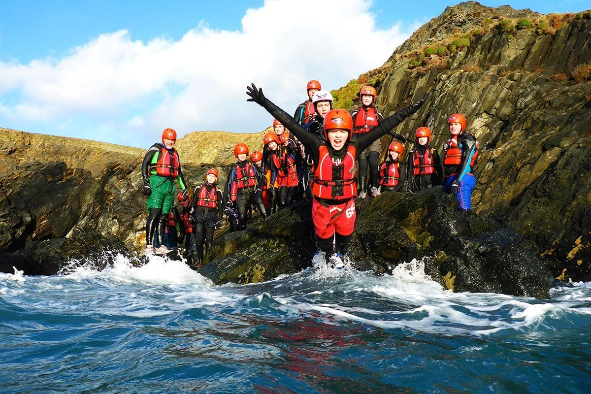 Children belly flopping into Wales' Celtic Sea. Our floaty Coasteering kit means you don't even need to be a strong swimmer!