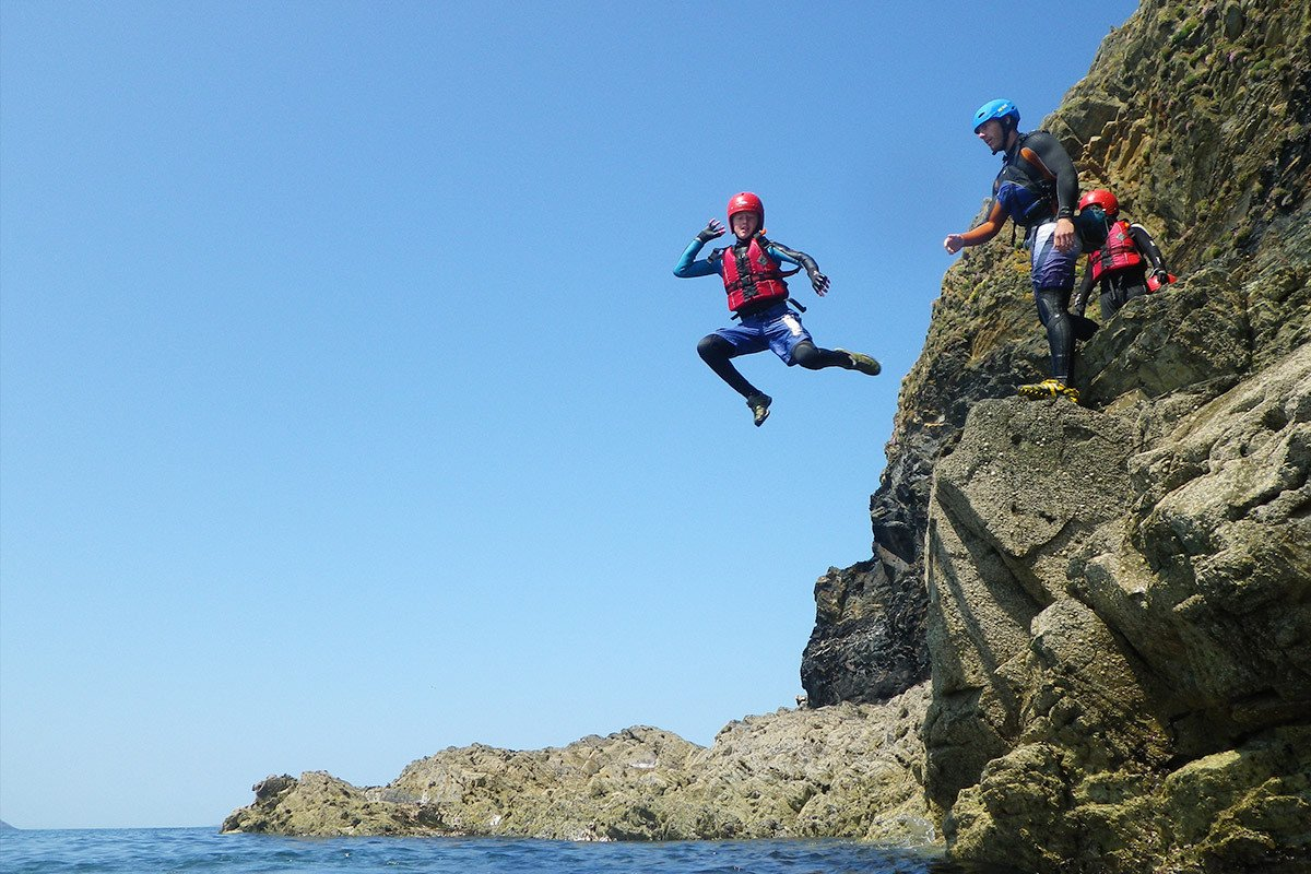 Cliff jumping adventure activity on a summers day in North Pembrokeshire Wales