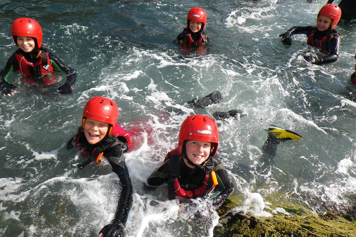 Children swimming in the Washing Machine, a Coasteering activity water feature.