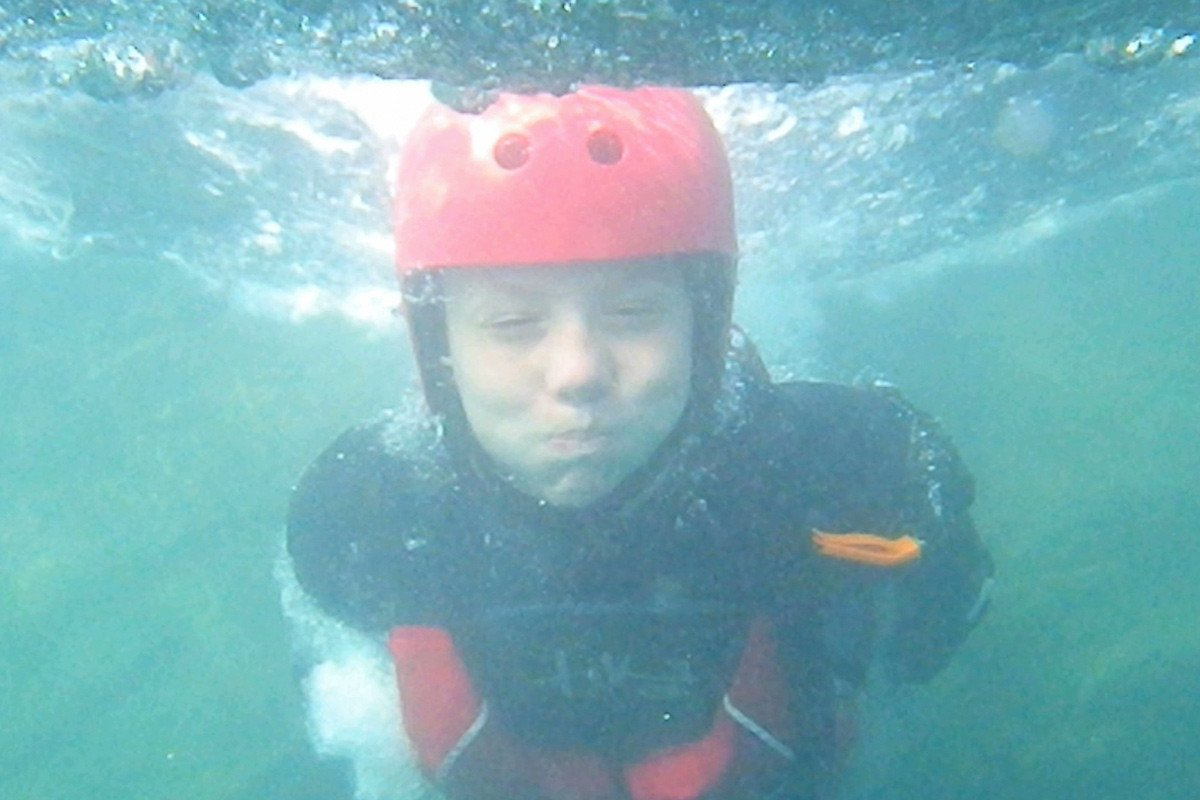 Children swimming underwater while Coasteering in Pembrokeshire Wales