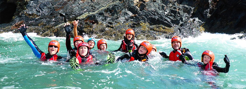 Family at Abereiddy Bay having fun Coasteering in Pembrokeshire Wales