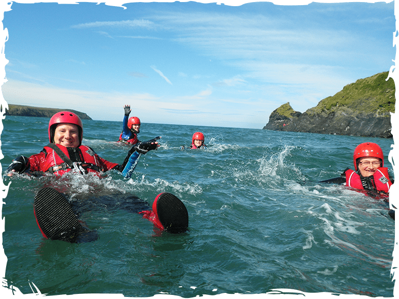 Family adventure swimming on a sunny summers day, while Coasteering in Pembrokeshire