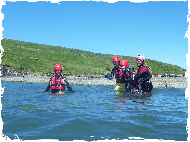 Entering the water off the beac while coasteering at Abereiddy Bay