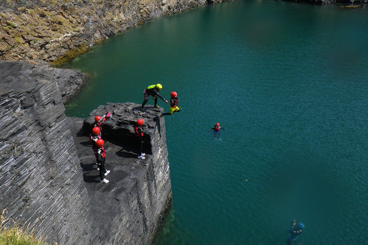 Family cliff jumping into the Blue Lagoon, Abereiddy, near St Davids Pembrokeshire Wales