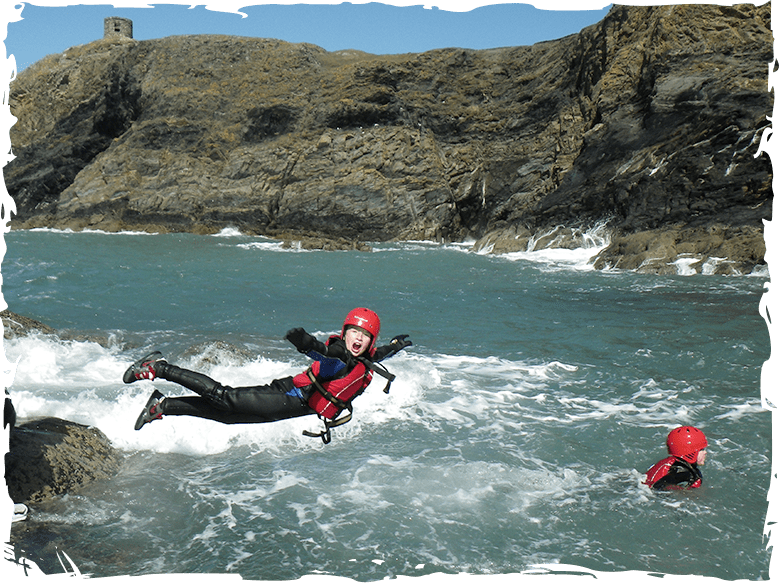 Children jumping into the sea while Coasteering near St Davids Pembrokeshire