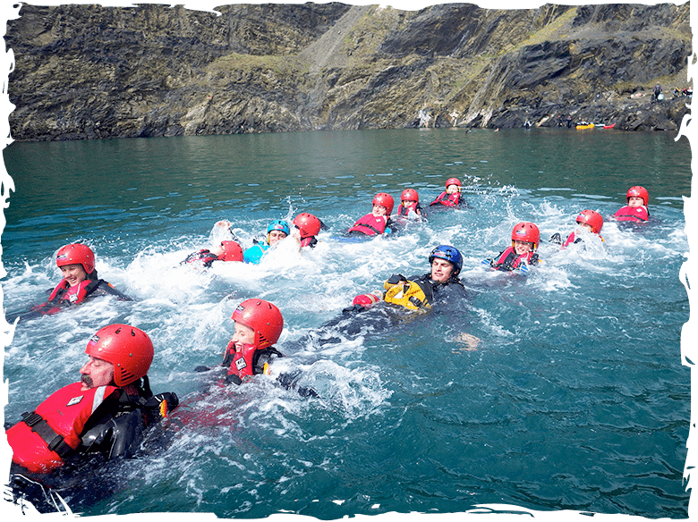 Family swimming in the Blue Lagoon while Coasteering at Abereiddy Pembrokeshire