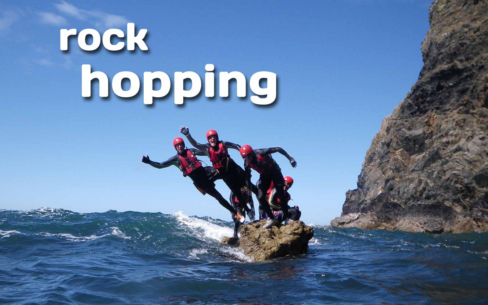 Adult groups leaping from a rock into Wales' Celtic Sea, summer sunshine & blue sky Coasteering
