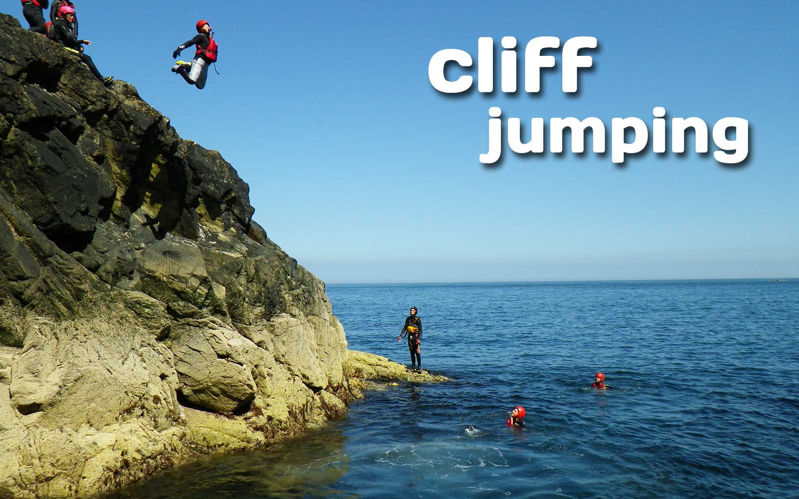 Coasteering cliff jumping, teenager leaping from the headland at Abereiddy bay, Pembrokeshire Wales