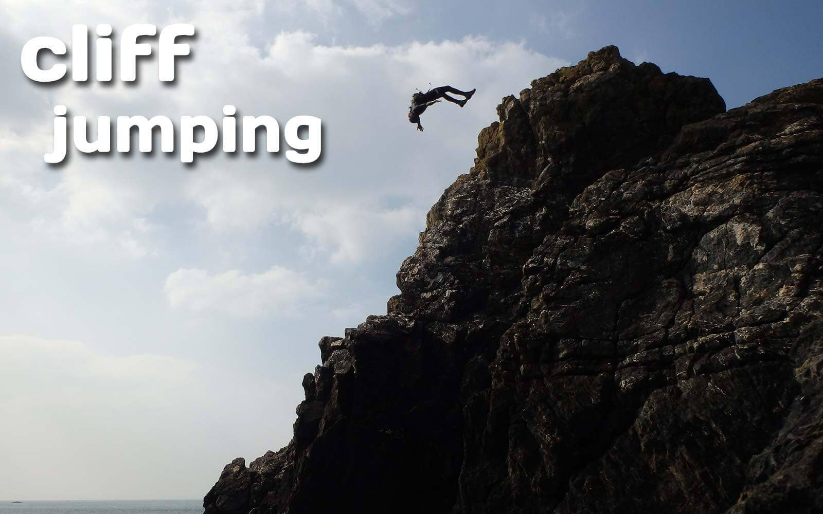 Coasteering cliff jumping from 10m, giant back flip from the headland at Abereiddy bay, Pembrokeshire Wales