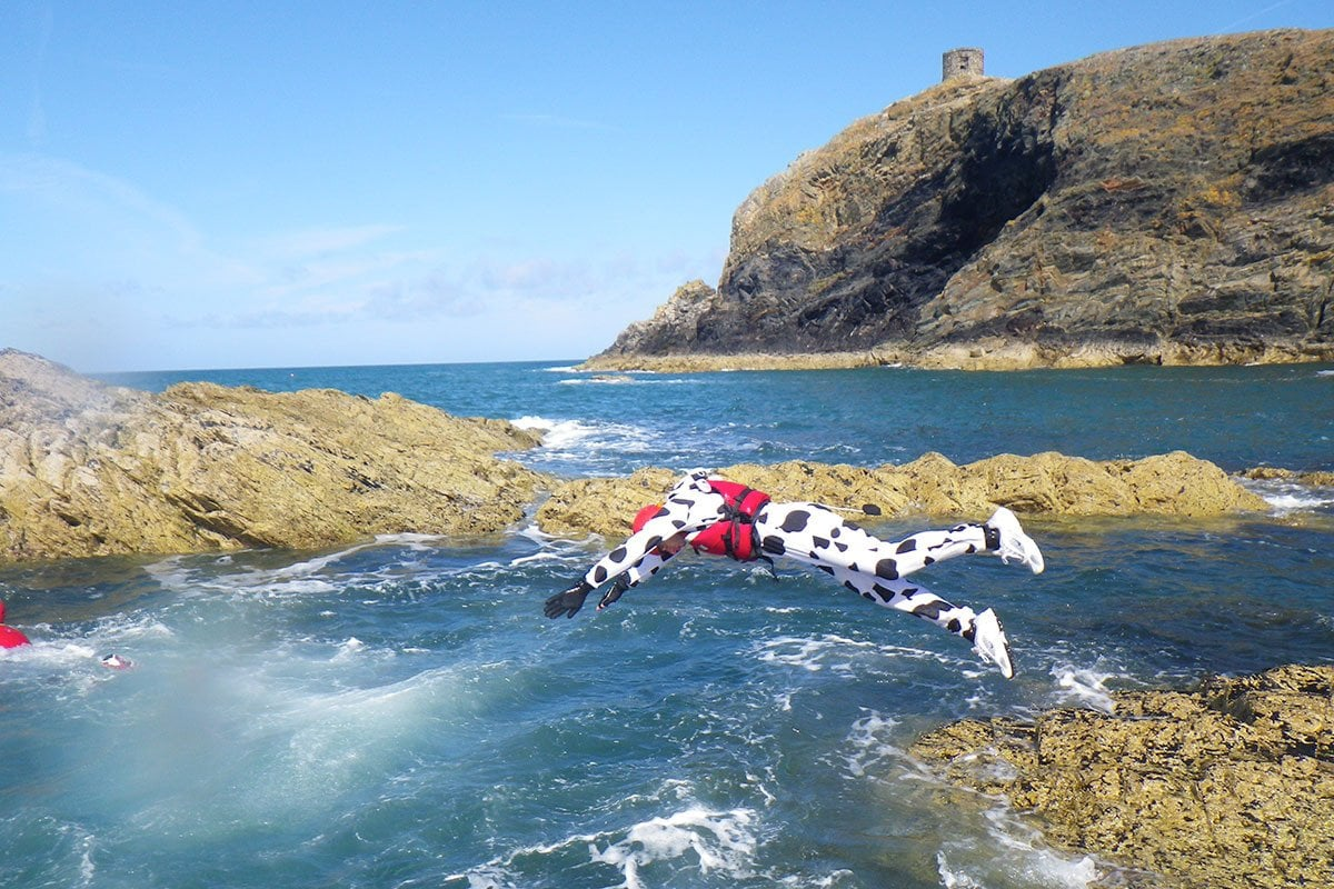 Best man diving into the sea, dressed as a cow while coasteering in near st davids