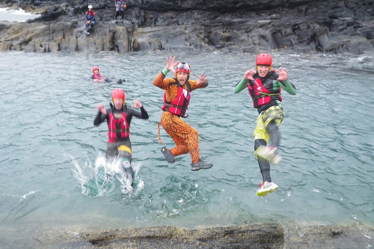 Stag dress as Tony the Coasteering tiger, jumping in the sea near St Davids Pembrokeshire