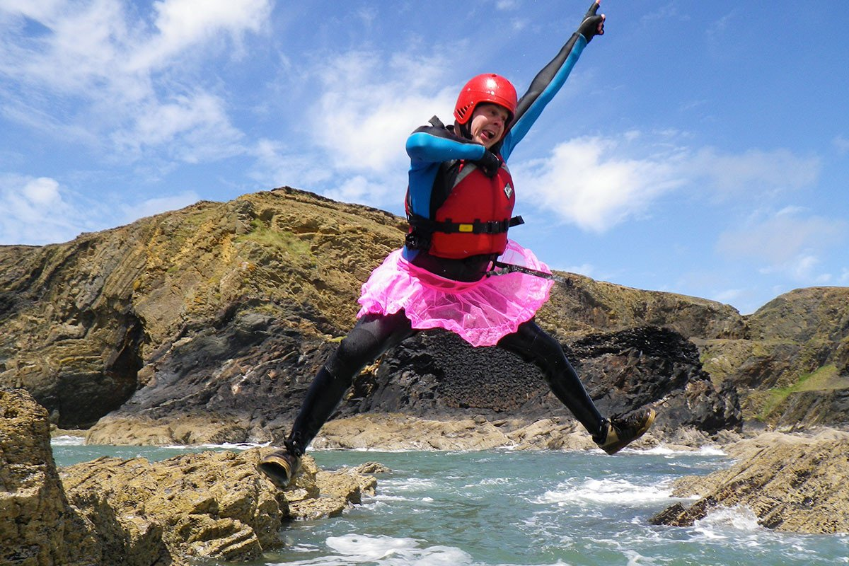 Stag dressed in a tutu cliff jumping while coasteering in Pembrokeshire Wales