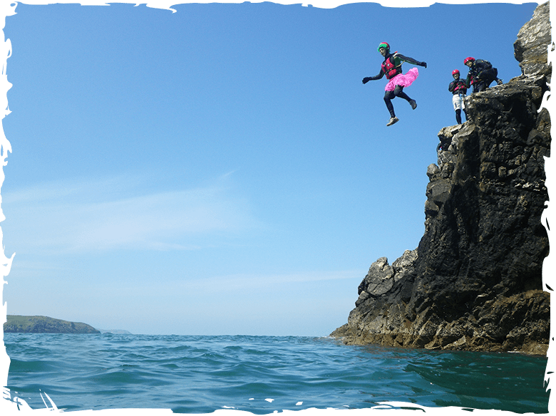 Stag cliff jumping while coasteering along the headland at Abereiddy bay