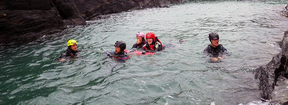 Accessible coasteering - people with disability can try coasteering at their own level & pace. Adventure swimming up a channel on the Pembrokeshire coast.