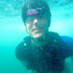 Nick underwater after a penguin dive coasteering in wales