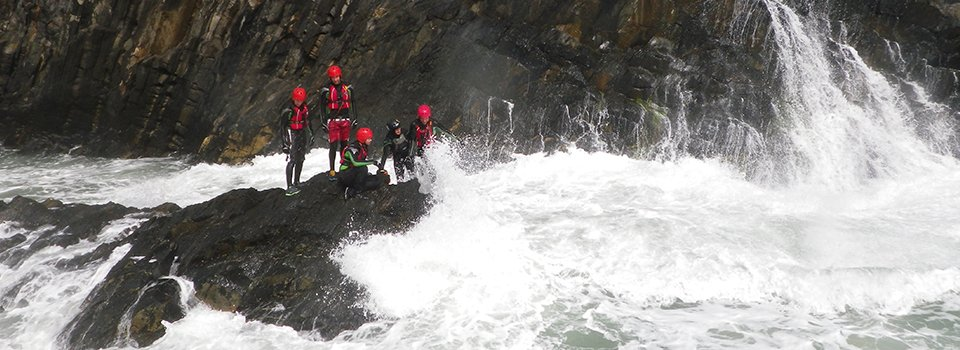 Visiting Pembrokeshire in the rain? Rainy day in West Wales? Here\\\\\\\'s a list of things to do in the rain, including attractions to visit and activities to do in Pembrokeshire. Featured image, a group of adults coasteering in the rain, with rough seas at Abereiddy Bay.