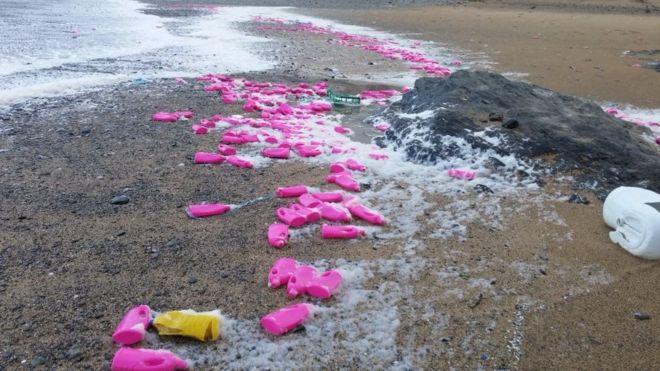 Bright pink bottles on Poldhu Beach