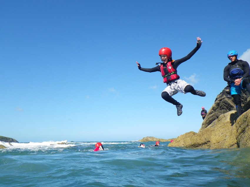 Families and children having a fun day out coasteering in Pembrokeshire Wales with Celtic Quest Coasteering