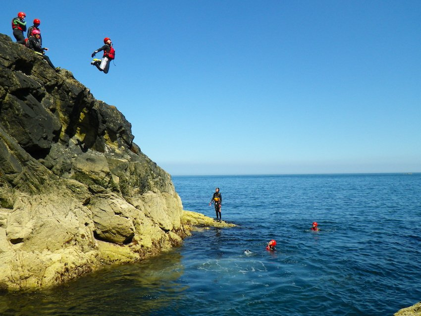 Teenager cliff jumping at Abereiddy. Children and teens adventure activities in Pembrokeshire, schools & youth groups Pembrokeshire South West Wales